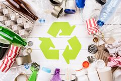 Top view of Different garbage materials with recycling symbol on white wooden table background. Recycle, World Environment Day and. Eco concept stock photo