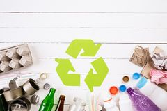 Top view of Different garbage materials with recycling symbol on white wooden table background. Recycle, World Environment Day and. Eco concept royalty free stock photo