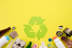 Top view of Different garbage materials with recycling symbol on yellow background. Recycle, World Environment Day and Eco concept.  stock image