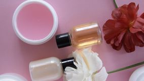 Top view of different hygienic/cosmetic products and flowers on fresh pink background. Wellness beauty treatment stock video footage