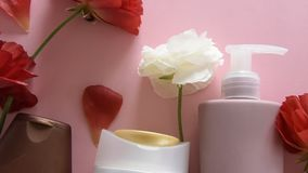 Top view of different hygienic/cosmetic products and flowers on fresh pink background. Wellness beauty treatment stock video