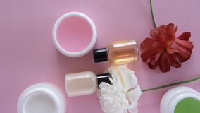 Top view of different hygienic/cosmetic products and flowers on fresh pink background. Wellness beauty treatment stock footage