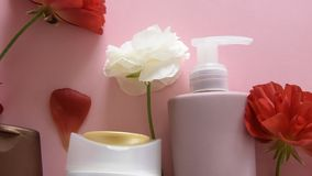 Top view of different hygienic products and flowers on fresh pink background. Wellness beauty treatment stock video footage