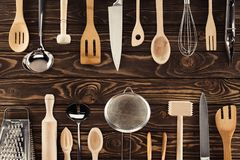Top view of different kitchen utensils placed in two rows. On wooden table Stock Photos