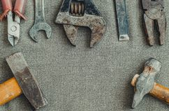 Top view different tools as hammer, screwdriver, spanner and pliers on textile background royalty free stock photography