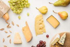 Top view of different types of cheese, grapes, pears, almond and baguette on white royalty free stock photos