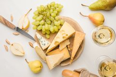 Top view of different types of cheese on wooden board surrounded by knife, fruits, almond, baguette and wine glasses on white royalty free stock image