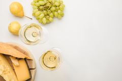 Top view of different types of cheese on wooden board, wine glasses and fruits on white stock photo