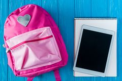 Top view of digital tablet with blank screen empty textbook and pink rucksack on blue wooden. Background stock image