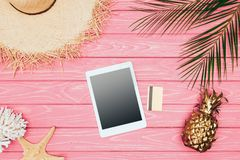 Top view of digital tablet with credit card and golden pineapple on pink. Wooden surface Stock Photo