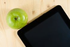 Top of view of digital tablet pc and green apple on wood table Royalty Free Stock Photo