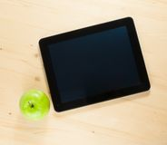 Top of view of digital tablet pc and green apple Stock Photos
