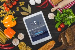 Top view of digital tablet with website and fresh raw ingredients. On wooden table Royalty Free Stock Images
