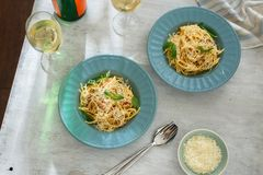 Top view dinner table. Two plate of pasta carbonara white wine. Top view dinner table. Two plate of pasta carbonara with glass of white wine on white wooden Royalty Free Stock Photography