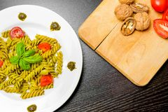 Top of view of dish of pasta with pesto genovese sauce and vegetables, tomato and basil on black wood table Royalty Free Stock Photography
