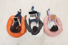 Top view of diverse people using smart gadgets. People and devices, students top view. Diverse friends in coworking using smart gadgets, preparing for exam at Stock Images