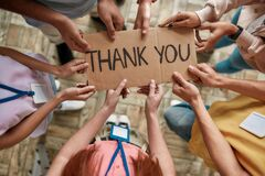 Top view of diverse young volunteers holding card with Thank you lettering while standing in charitable organization