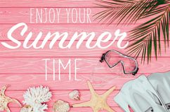 Pink wooden surface with lettering. Top view of diving mask with flippers on pink wooden surface with enjoy your summer time lettering royalty free illustration