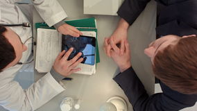 Top view of Doctor reviewing x-ray with patient