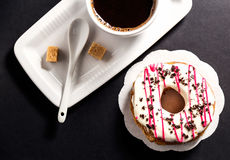 Top view of donut and cup coffee on black background Stock Image
