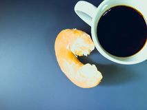 Top view from donut after eat with black coffee in white cup fro. M morning time with blue tone background royalty free stock photo