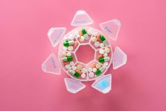 Top view daily doses pills in a plastic container on pink. Background stock image