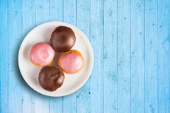 Top view of doughnuts with sweet topping on a plate Stock Photos