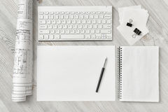 Top view of draftsman's workplace with keyboard, paper, pen, notebook and rolled draft. Top view of a draftsman's workplace with a keyboard, a sheet of paper royalty free stock photography