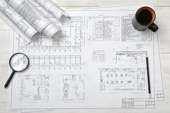 Top view of draftsman's workplace with plan, magnifier, pencil, mug coffee and rolled drafts. Top view of a draftsman's workplace with a plan, a magnifier, a royalty free stock photo