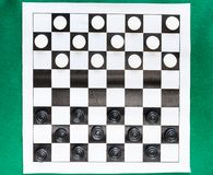 Top view of draughts on black and white sheet. Top view of draughts on black and white checkered sheet board on green baize table stock photos