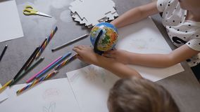 Top view. At the drawing lesson, the children sit at the table and draw with the teacher. Children paint with pencils stock footage