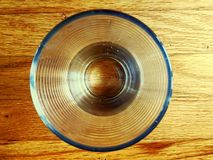Top view of a drinking glass on a wooded table. Clear glass sitting on a wood table Stock Photo