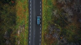 Top view drone follows black SUV car driving along highway in cloudy autumn forest on road trip, adventure concept.