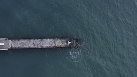 Top view from drone man lying on sea pier on splashing water waves background. Top view man lying on edge sea pier and splashing water waves. Drone flying over stock video footage