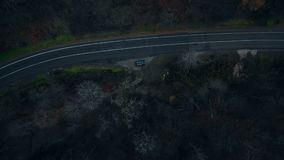 Top view drone rotating directly above black car standing at dark dangerous mystic forest road, horror and fear concept.