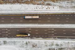 Top view from drone to winter asphalt highway or motorway road in countryside with car truck traffic driving fast.  royalty free stock photo