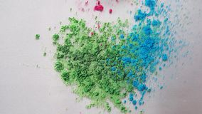 Top view of dry colorful inks falling in white liquid substance. Beautiful iridescent background of green, blue and rose stock video footage