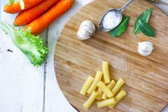 Top view of dry rigatoni pasta and some vegetables over wooden board. Top view of dry rigatoni pasta and some vegetables over wooden board royalty free stock images