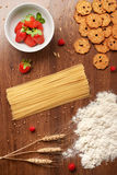 Dry spaghetti pasta, flour, wheat, homemade cookies and berries royalty free stock images