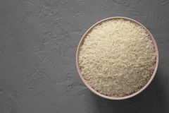 Top view, dry white rice basmati in a pink bowl over gray surface. Flat lay, overhead, from above. Copy space royalty free stock images