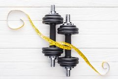 Top view of dumbbells and yellow measuring tape. On wooden surface royalty free stock images