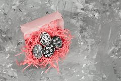 Dyed eggs with black and white geometric pattern in a decorative pink nest on a concrete background. Top view dyed eggs with black and white geometric pattern in royalty free stock images