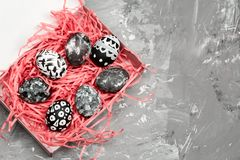 Dyed eggs with black and white geometric pattern in a decorative pink nest on a concrete background. Top view dyed eggs with black and white geometric pattern in stock images