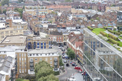 Top view East London cityscape over apartments, offices, shops. Aerial view of east London busy urban district with densely built up houses, shops, offices Royalty Free Stock Images