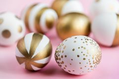 Top view of easter eggs colored with golden paint. Various striped and dotted designs. Pink background. Royalty Free Stock Photos