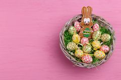 Top view of Easter eggs and a gingerbread in the shape of a rabbit in a wicker basket on a bright pink background. Stock Photo