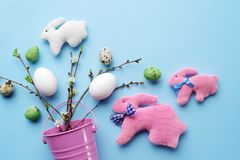Top view of Easter eggs and handmade rabbits with spring twigs on a pastel blue background. Easter eggs and handmade rabbits with spring twigs and flowers on a Stock Photos