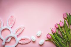 Top view of Easter eggs, pink tulips and two white fluffy bunny ears over pink background. Easter concept background.Copy space. Stock Photos