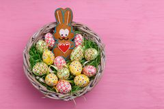 Top view of Easter quail eggs and a a cookie shaped like a bunny in a wicker basket on a bright pink background. Stock Photos