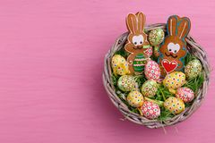 Top view of Easter quail eggs and cookies shaped like a bunny in a wicker basket on a bright pink background. Royalty Free Stock Images